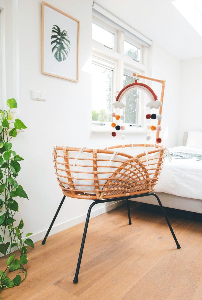 Bohemian Baby Roma Vintage rotan wieg in slaapkamer naast plant met baby mobiel