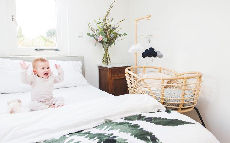 Bohemian Baby Roma natural natuurlijk rotan wieg met lachende baby zwaaiend op bed