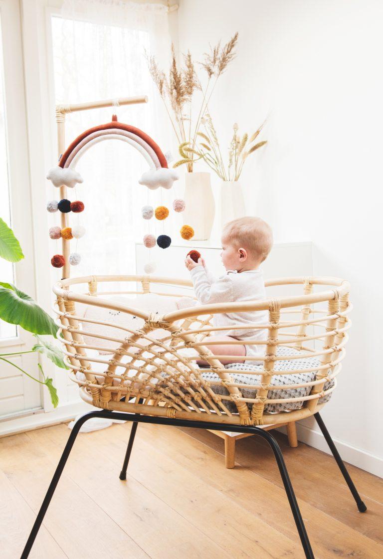 Bohemian Baby Roma natural natuurlijk rotan wieg met spelende baby met mobiel